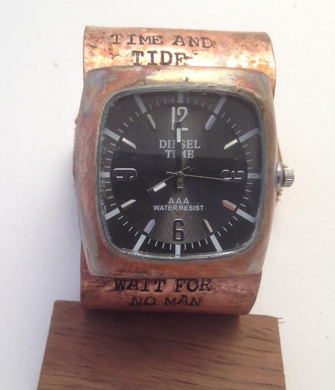 Black face tank watch on copper cuff